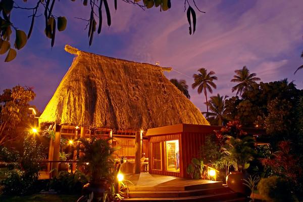 A bure lit up at night at Namale Resort Fiji